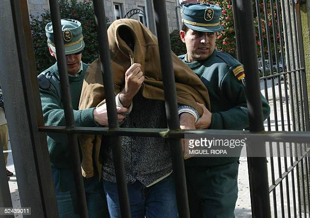 A man who was arrested during an international Internet child pornography sweep is escorted by a policeman as he arrives at the Court of Caldas de...