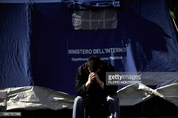 Man who was evacuated from his home following the April 6 earthquake sits at the entrance of a tent in a camp set up in the Abruzzo capital L'Aquila...