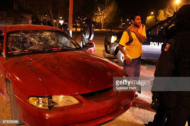 Man who was injured when his windshield was smashed with rocks speaks with the police on March 21, 2010 in Juarez, Mexico. The border city of Juarez...