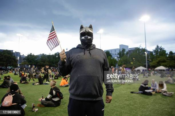 TOPSHOT A man who wished to remain anonymous is pictured wearing a raccoon mask in an area being called the Capitol Hill Autonomous Zone located...