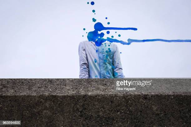 A man whose head is a blue paint and flows