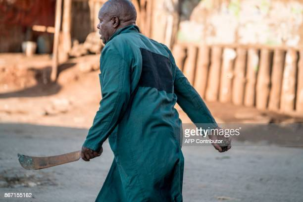 A man wielding a machete walks in the Kawangware district of Nairobi on October 27 2017 during clashes between different communities during following...