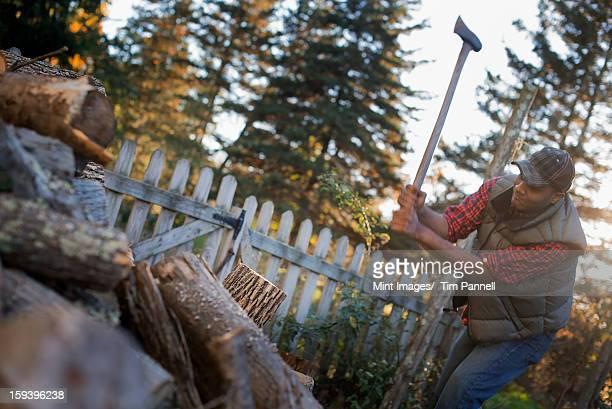 Ein Mann Essen mit einer Axt, und hacken Holz, teilen