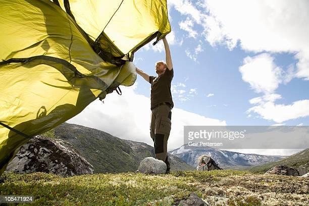 Man wildcamping, setting up tent