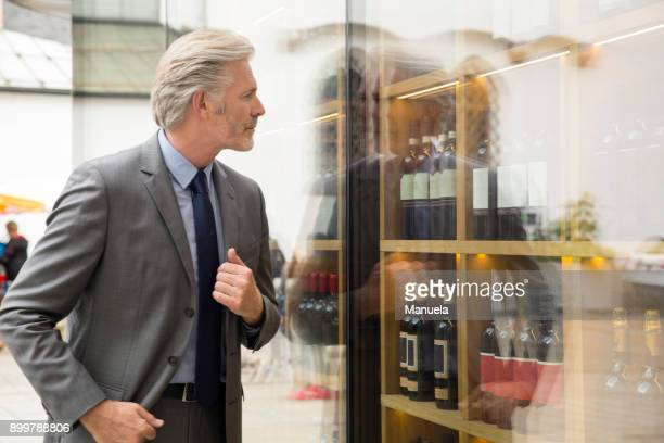 man window shopping in wine shop window - desire stock pictures, royalty-free photos & images
