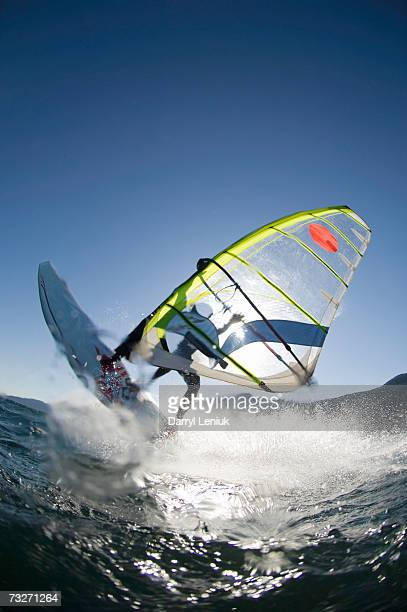 Man windsurfing in front of sun