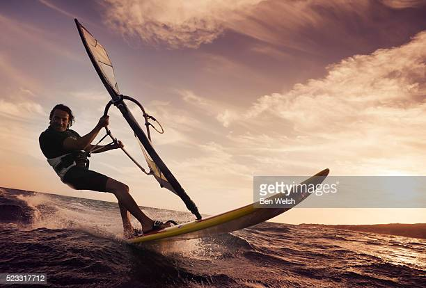 man windsurfing on ocean - windsurfing stock pictures, royalty-free photos & images