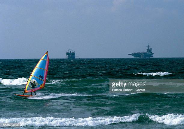 A man windsurfs in the Mediterranean Sea near two military vessels American armed forces sent troops aboard the USS John F Kennedy aircraft carrier...