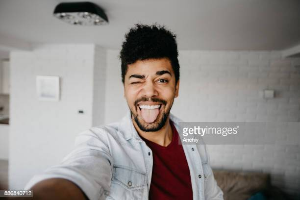 Man winking to a camera and taking a selfie