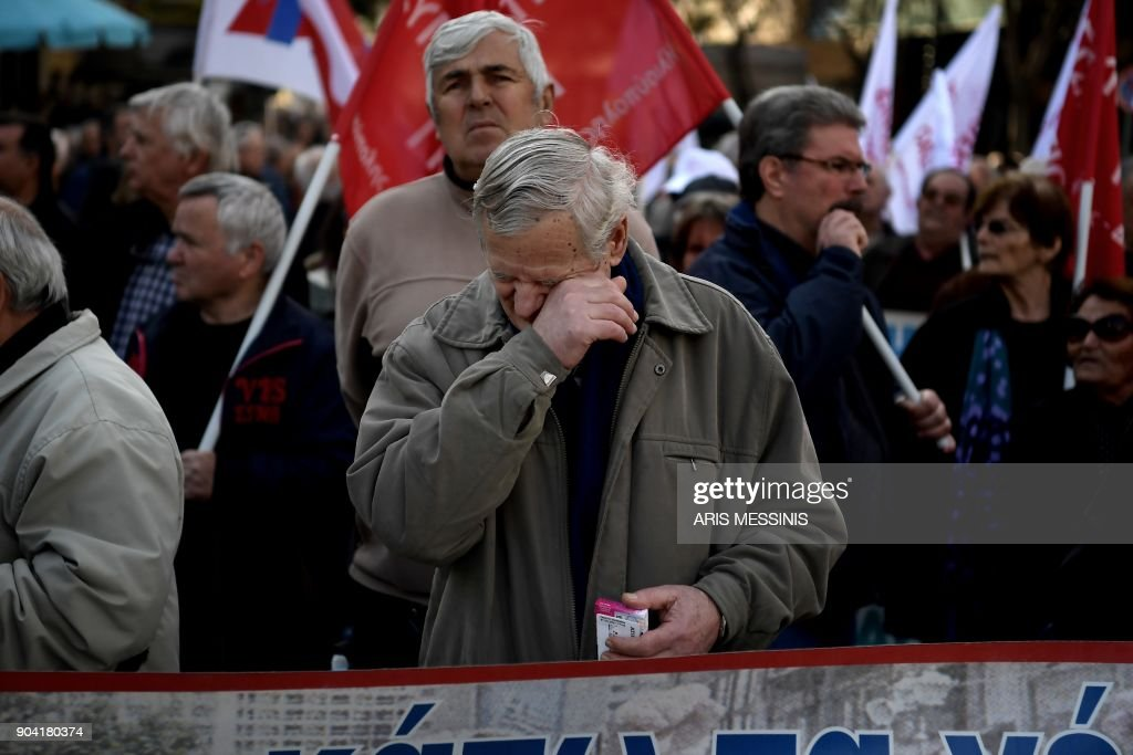 A man wipes his eye during a demonstration against changes to a 36-year-old industrial action law demanded by the country's creditors in Athens on January 12, 2018. /