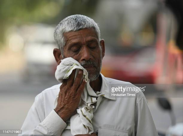 A man wipes his face with a cloth on a hot summer day as temperatures in the capital reach 45 degree celcius at Deen Dayal Upadhyay Marg on May 31...
