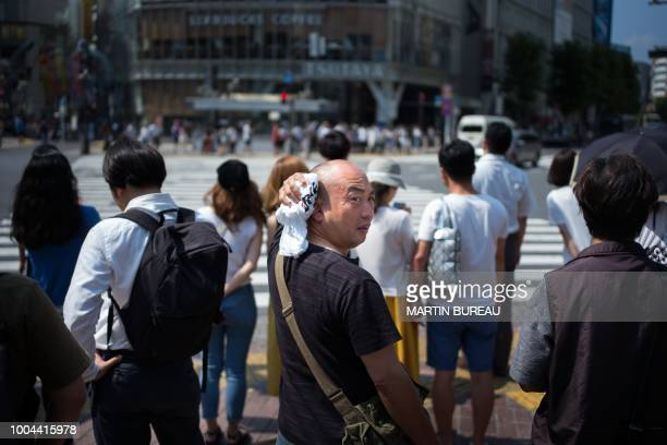TOPSHOT A man wipes perspiration from his head in Tokyo on July 24 as Japan suffers from a heatwave An 'unprecedented' heatwave in Japan has killed...