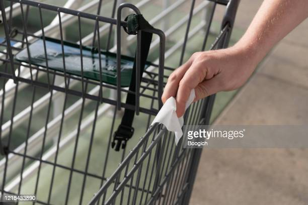 man wipes shopping cart with disinfecting towel during pandemic in miami florida - wet wipe stock pictures, royalty-free photos & images