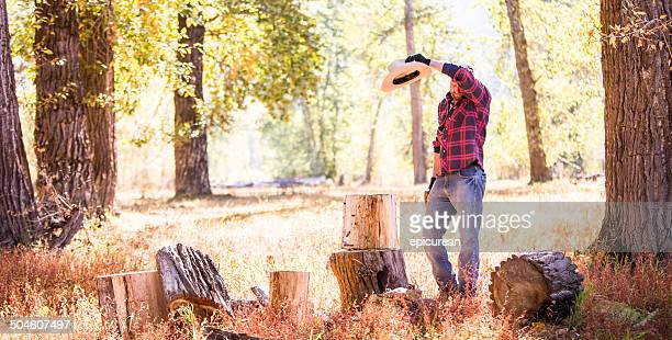 Man wipes sweat from brow while resting from chopping wood