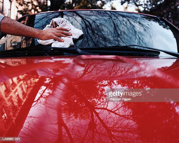 Man wiping car windshield with cloth, close-up