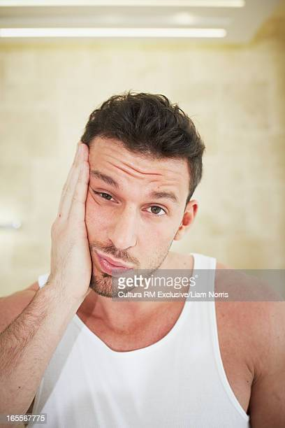 Man wiping his face in bathroom