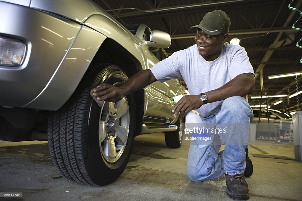 Man wiping SUV tires : Stock Photo