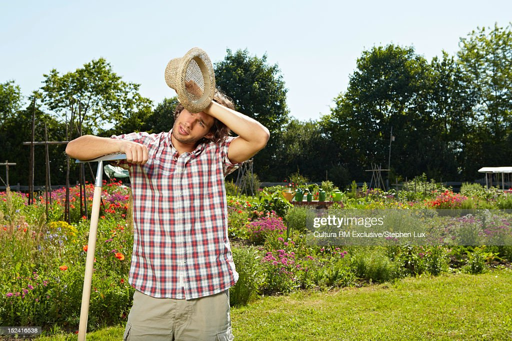 Man wiping sweat form forehead in yard : Stock Photo