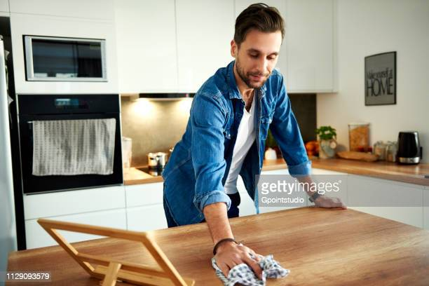 Man wiping table in kitchen