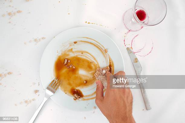 man wiping up sauce from plate - cleaning after party stock pictures, royalty-free photos & images