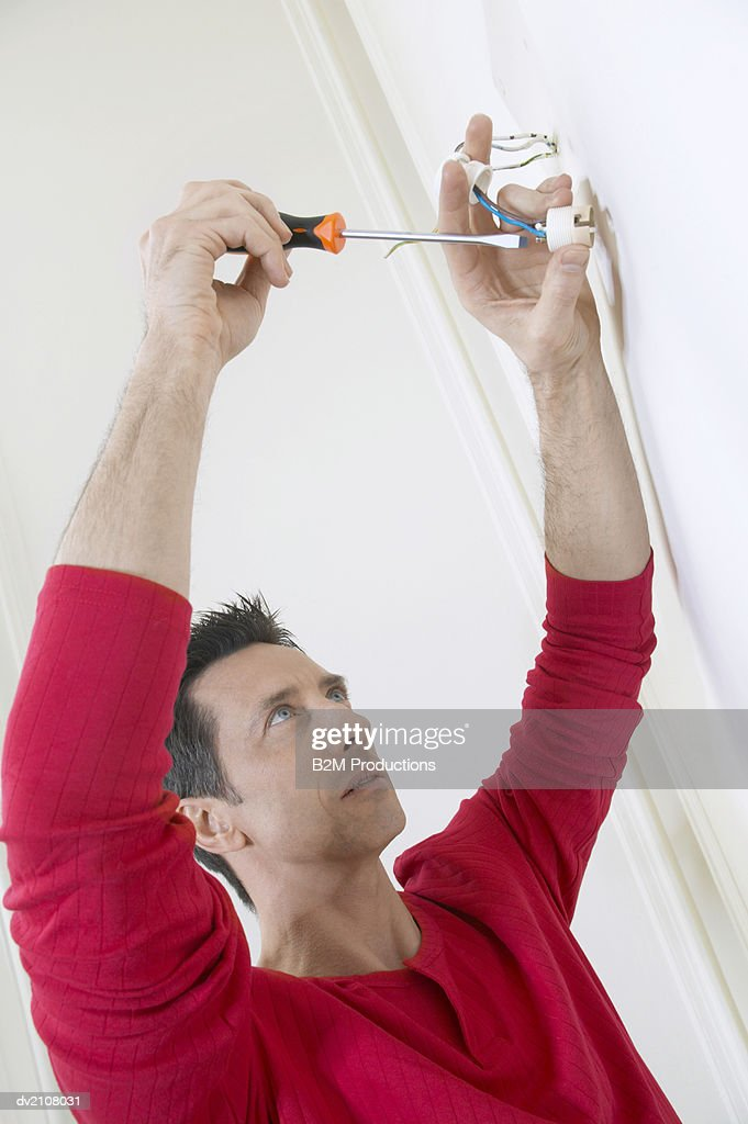 Man Wiring a Socket in a Wall : Stock Photo