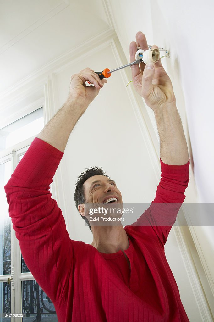 Man Wiring an Electrical Socket in a Wall : Stock Photo
