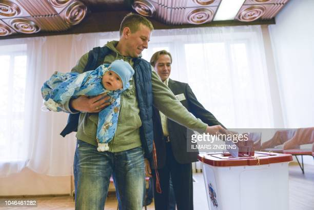 A man with a baby casts his ballot at a polling station in Ogre Latvia during general elections on October 6 2018