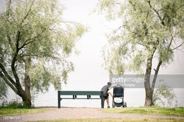 Man with a baby stroller sits by the sea in Helsinki, Finland on August 7, 2020. / Finland OUT