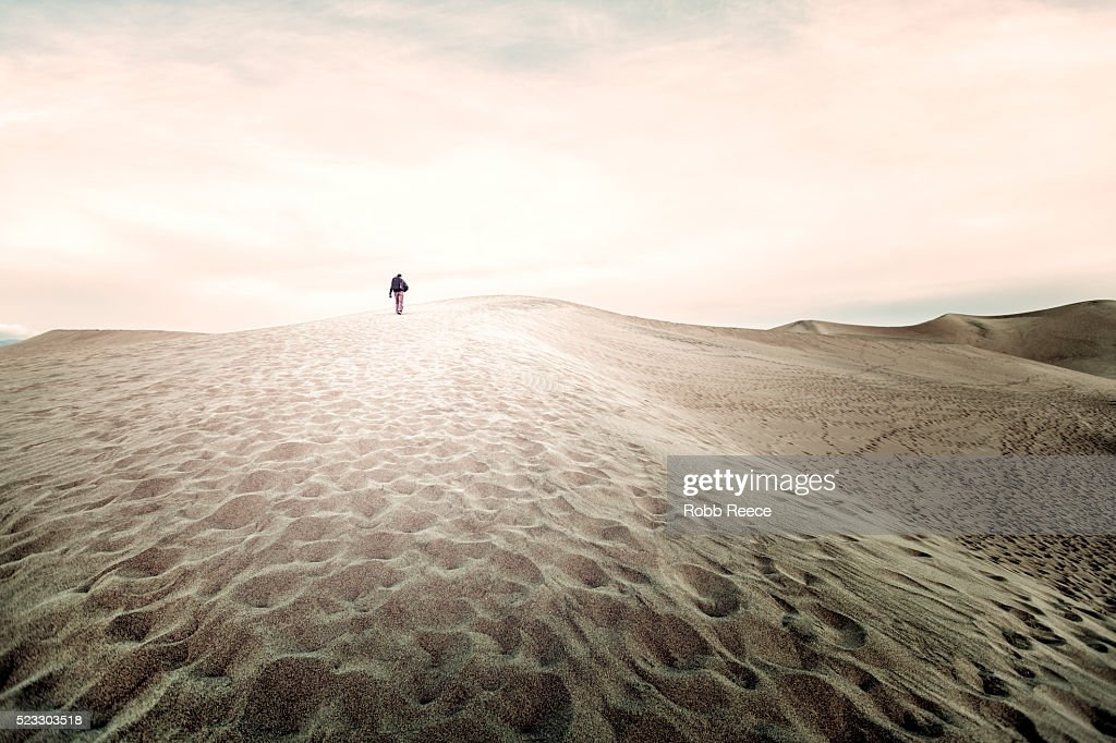 A man with a backpack hikes up a large sand dune in Death Valley, CA : Stock Photo