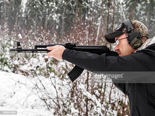 Man with a baseball cap and ear protection shooting an AK47 rifle in the woods with snow on the ground.