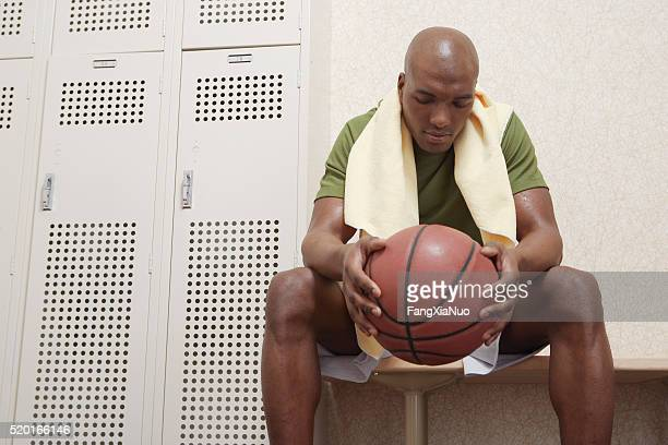 Man with a basketball in a locker room
