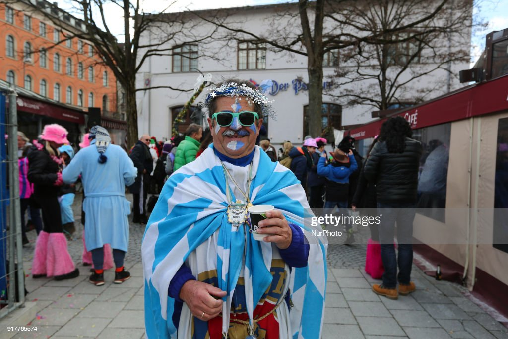 A man with a bavarian costume is seen in the Munich Carnival. The man wears bavarian flag, is painted with the bavarian colours white and blue and wears bandana with wihite and blue flours. Under the flag he wears something from the brewery Paulaner.