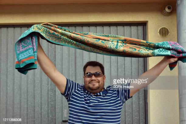 A man with a beach towel dances on the terrace of his house to encourage his neighbours during the confinement amid Coronavirus crisis Residents of...