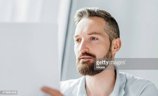 man with a beard looking over papers
