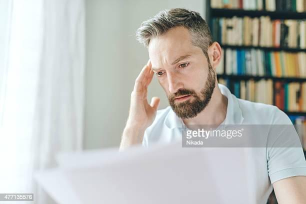 Mann mit Bart über Zeitungen