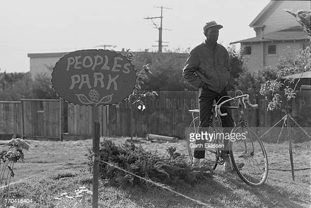 A man with a bicycle stands beside a sign at the People's Park II Berkeley California June 2 1969 The Annex located on the Hearst Corridor between...