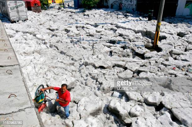 Man with a bike walks on hail in the eastern area of Guadalajara, Jalisco state, Mexico, on June 30, 2019. - The accumulation of hail in the streets...