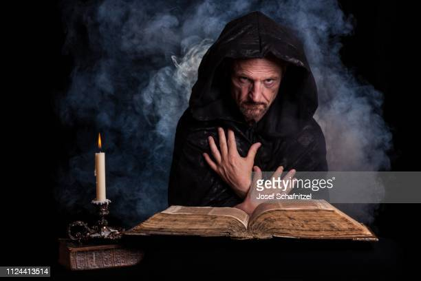 man, with a black hooded coat, in front a burning candle and an old book, germany - cult stock pictures, royalty-free photos & images