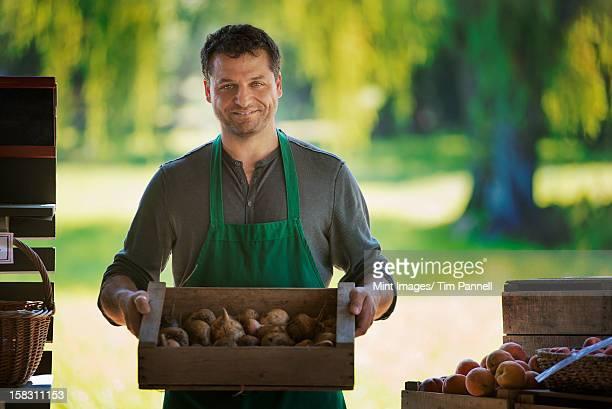 Um homem com uma caixa de seleção de frutas fresco.