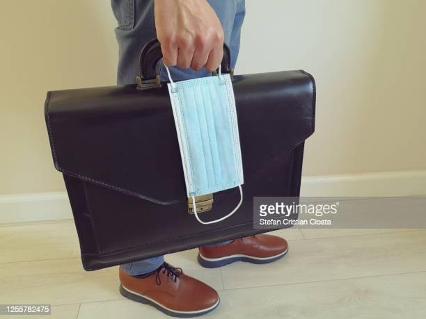 man with a briefcase and a surgical mask - devolución del saque fotografías e imágenes de stock