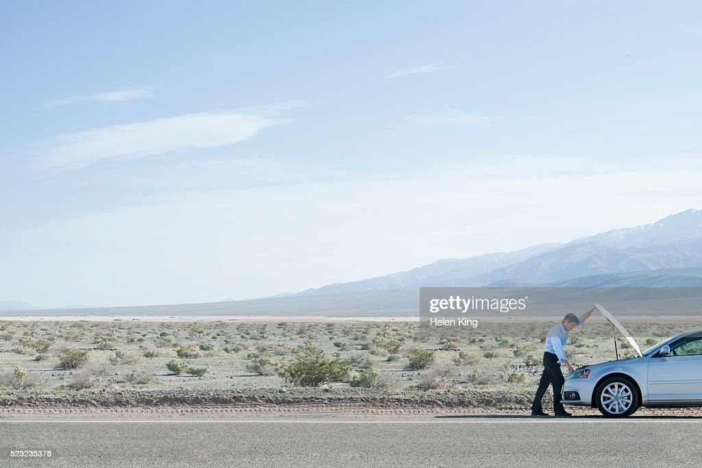 Man With A Broken Down Car In The Desert Stock Photo