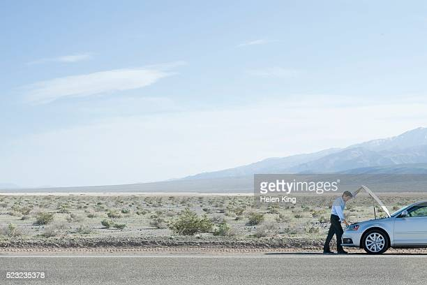 man with a broken down car in the desert - broken down car stock pictures, royalty-free photos & images