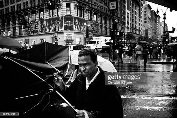 CONTENT] A man with a broken umbrella crossing 34th Street Broadway in NYC on a rainy windy fall day