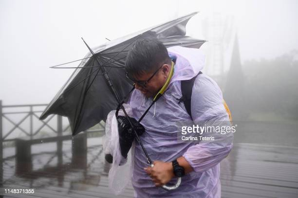 man with a broken umbrella in a storm - blowing stock pictures, royalty-free photos & images