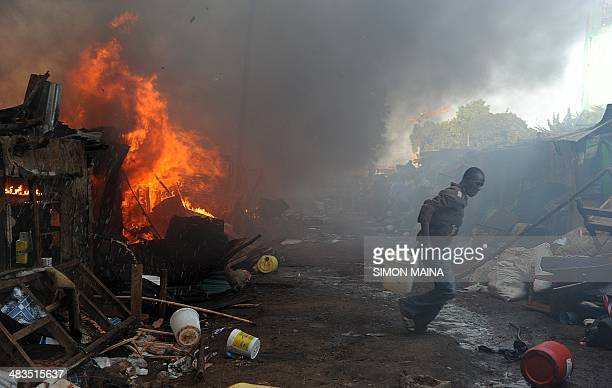 A man with a bucket of water works to put out a fire caused by an electrical fault from one of the residences as it razes houses in Deep Sea slum in...