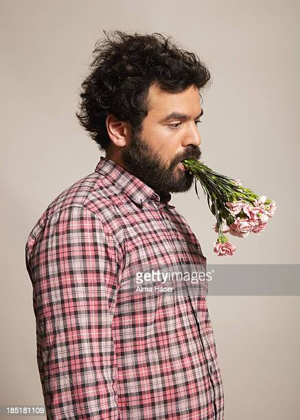 Man with a bunch of carnations in his mouth