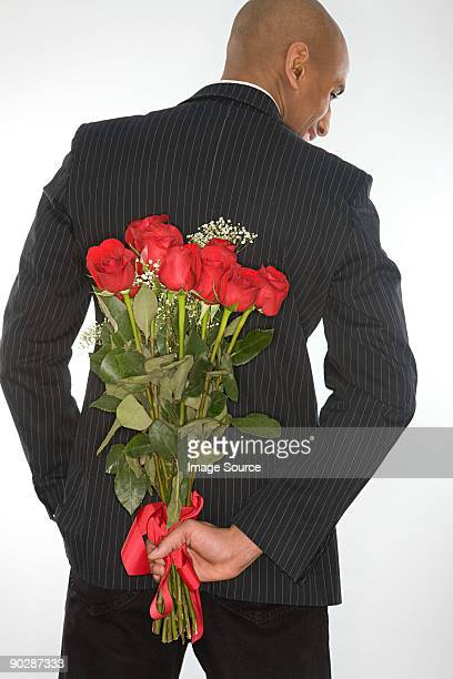 man with a bunch of roses behind his back - black rose stock pictures, royalty-free photos & images