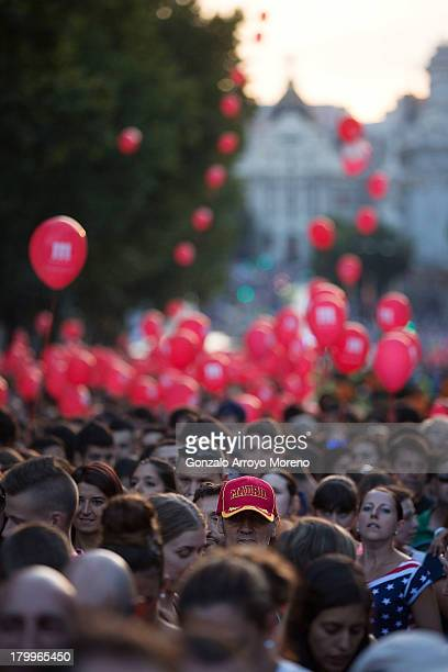 A man with a cap of Madrid in the middle of the crowd waiting for the voting of Madrid 2020 Candidancy at Puerta de Alcala with Gran Via street in...