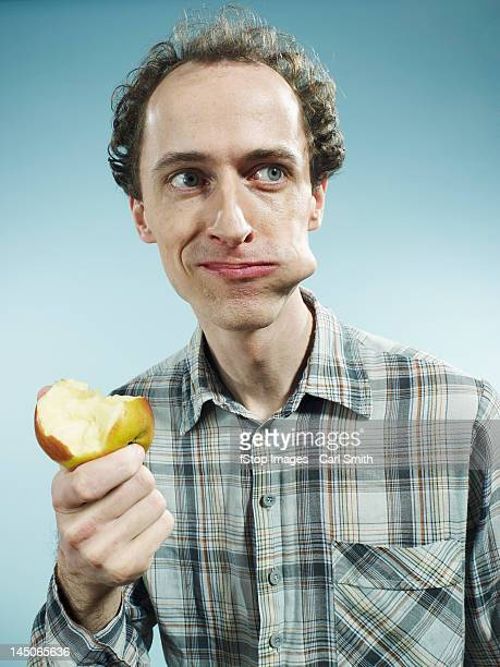 a man with a cheek bulging with a bite of apple, looking to the side - greedy smith stock pictures, royalty-free photos & images