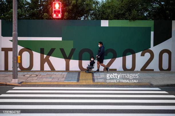 Man with a child walks past a poster for the 2020 Tokyo Olympics along a street in Tokyo on May 10, 2021.